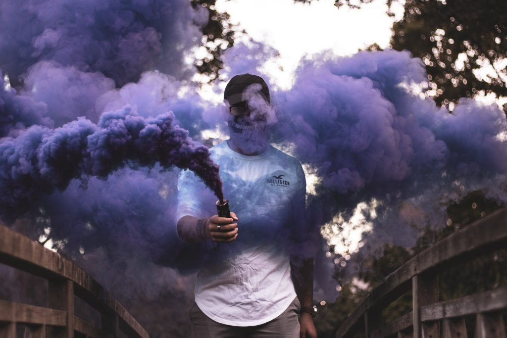 A person shrouded in purple smoke.