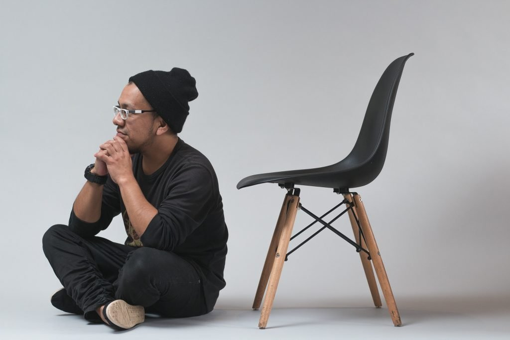 A person sitting on the ground next to a chair.