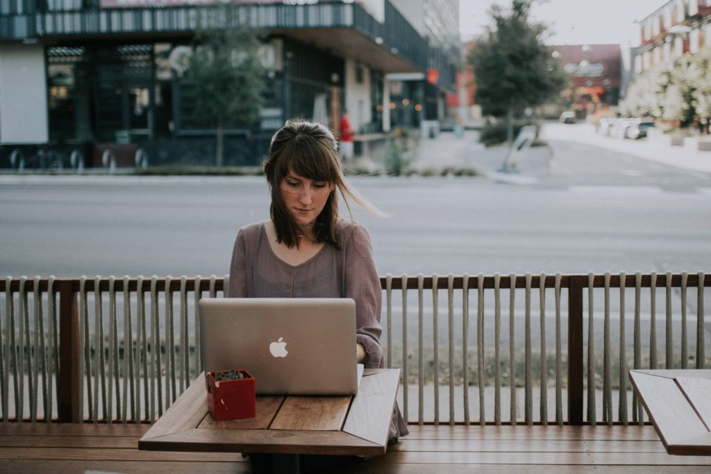 A woman sitting on a bench with her computer.