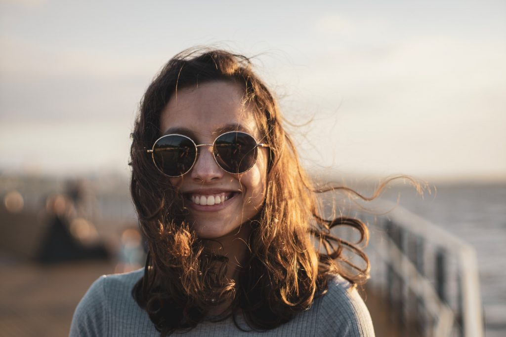 A person smiling at sunset.