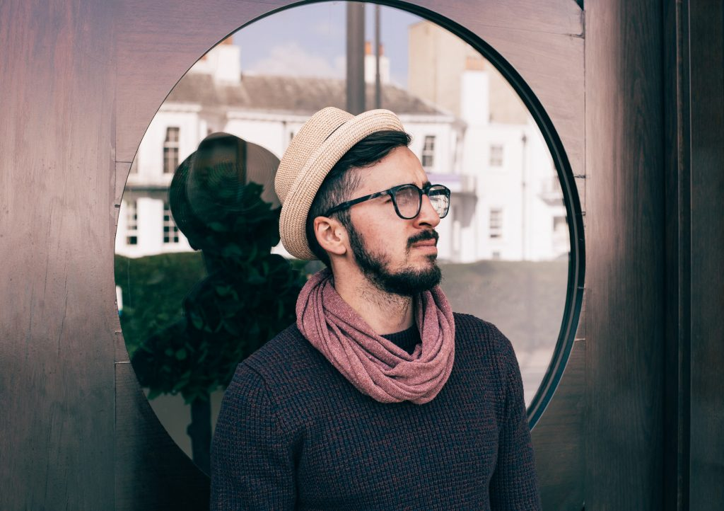 A person wearing a scarf before a circular window.