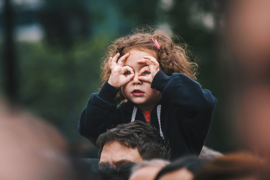 A kid putting their hands up to their face in a silly gesture.