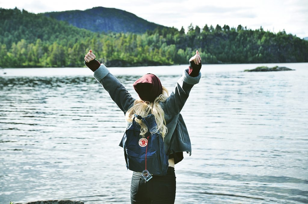 A person with outstretched arms by a lake.