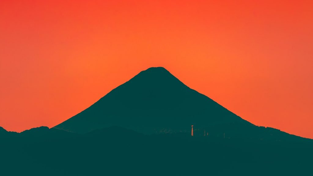 A red sky. A black silhouette of a mountain.