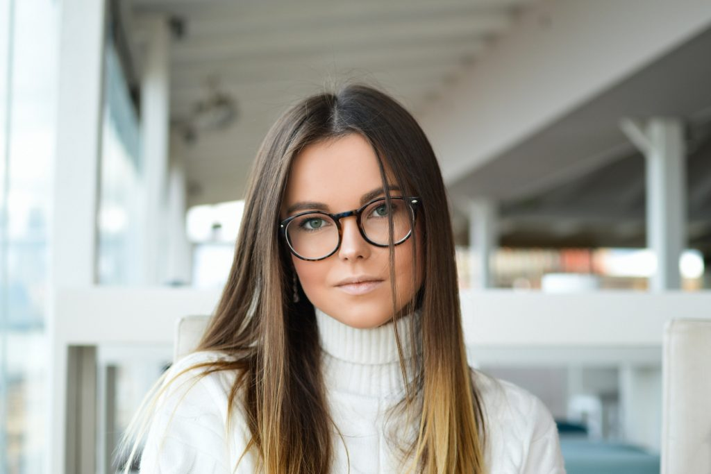 A person wearing glasses and a white sweater.