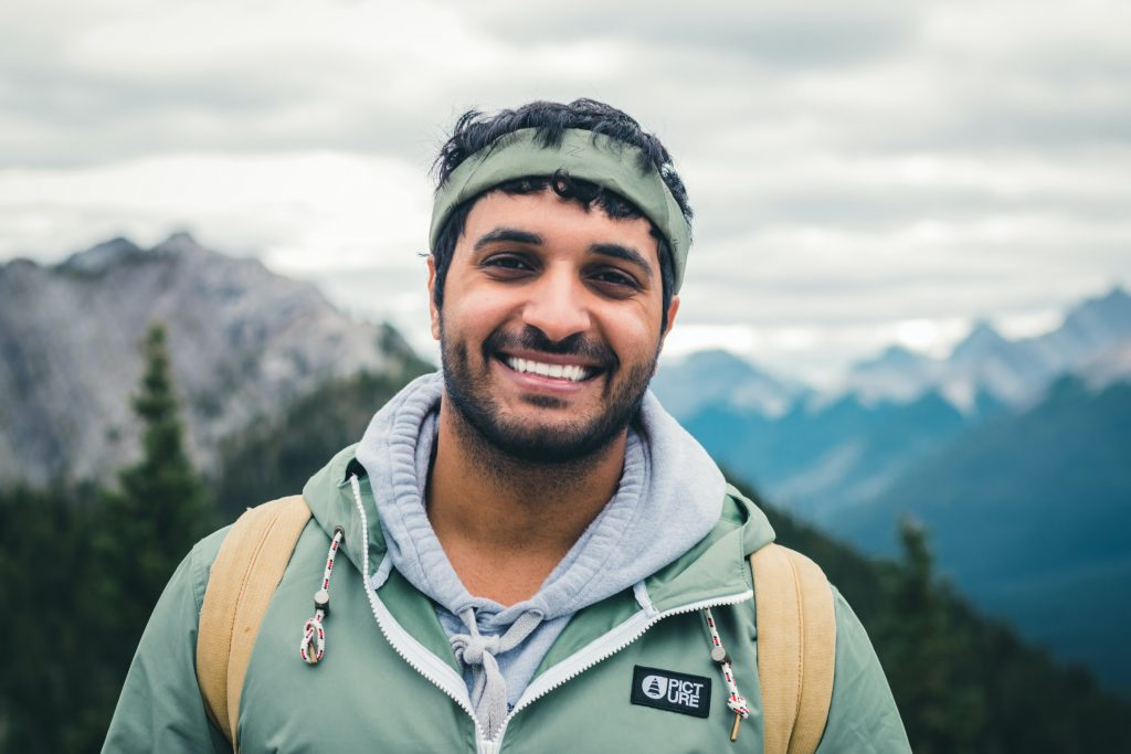A person on a hike wearing a green sweatshirt.
